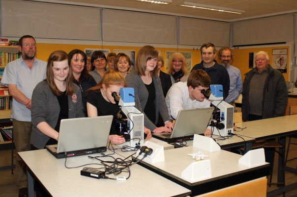 Members of the Parent Council look on as the microscopes are used by S6 Biology students
