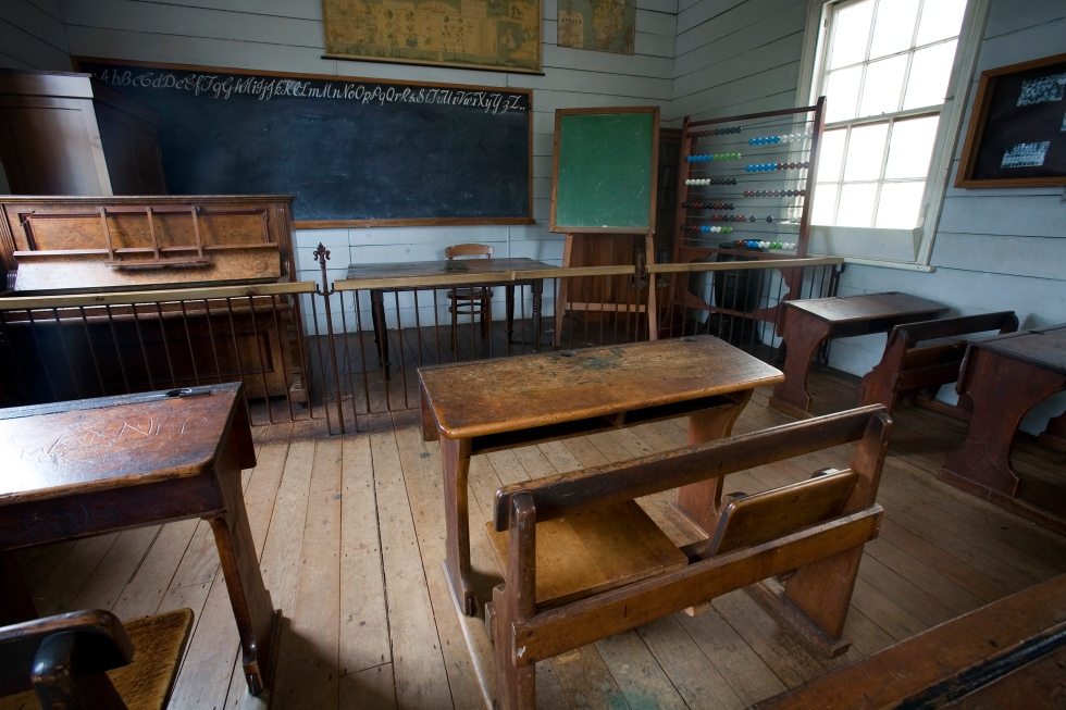 A nineteenth (XIX) century (1800s) classroom with wooden benches, a piano and a blackboard.Auckland, New Zealand